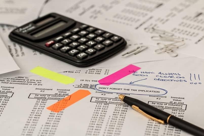 Una calculadora, un bolígrafo y algunos papeles.