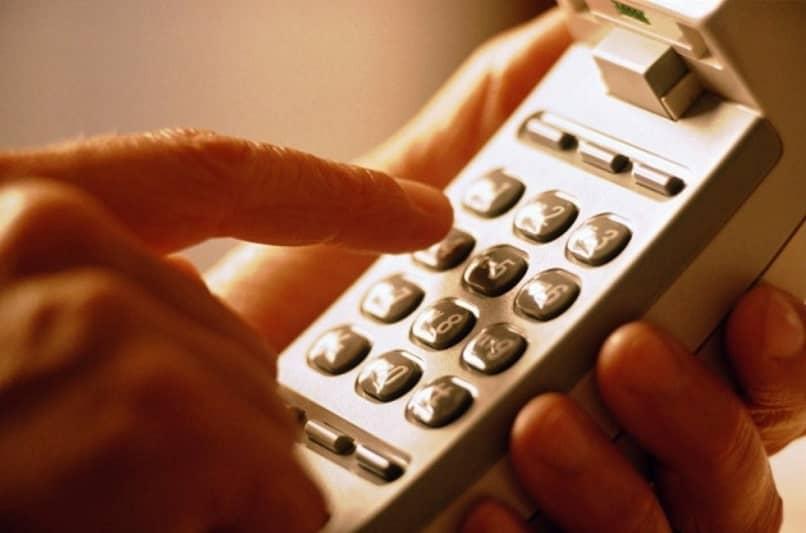 Manos sosteniendo un teléfono analógico