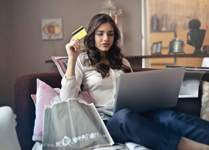 Chica guapa con tarjeta en mano frente a su computadora portátil