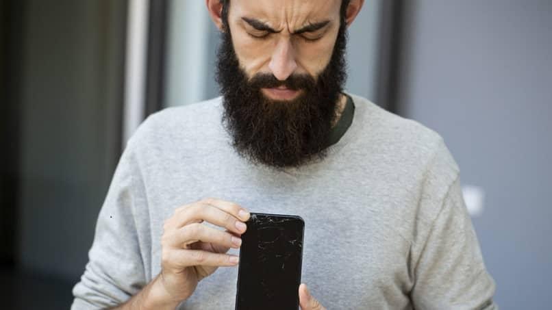 Hombre sujetando celular con pantalla rota