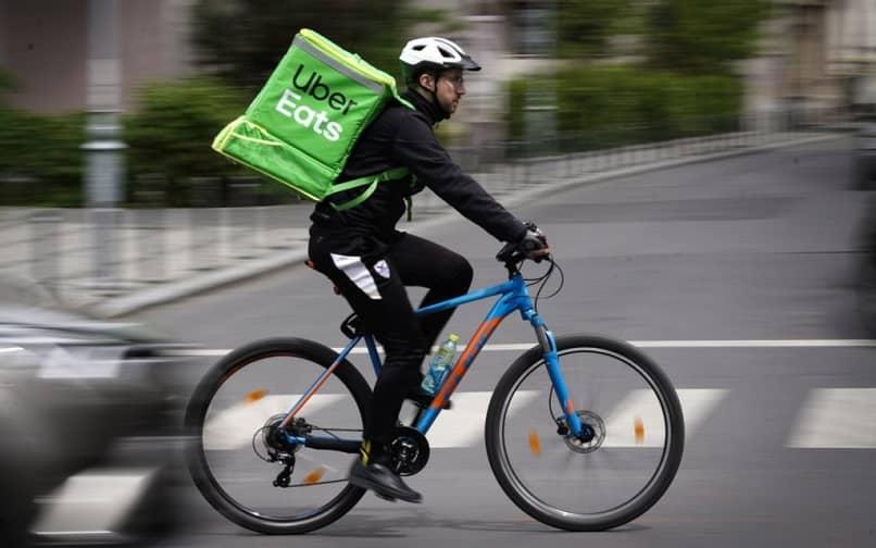 Repartidor de Uber come una bicicleta de carretera