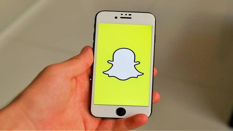 sosteniendo un teléfono Snapchat