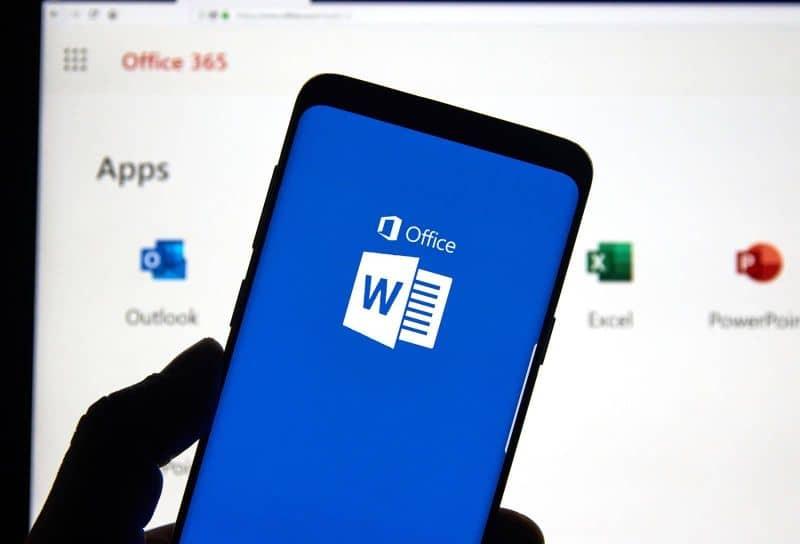 Smartphone en mano con Word en pantalla y programas de Office en segundo plano.