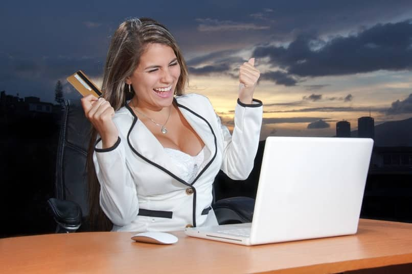 hermosa mujer sonríe frente a su computadora portátil