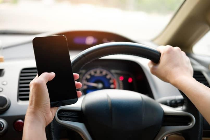 conductor uber con móvil en mano