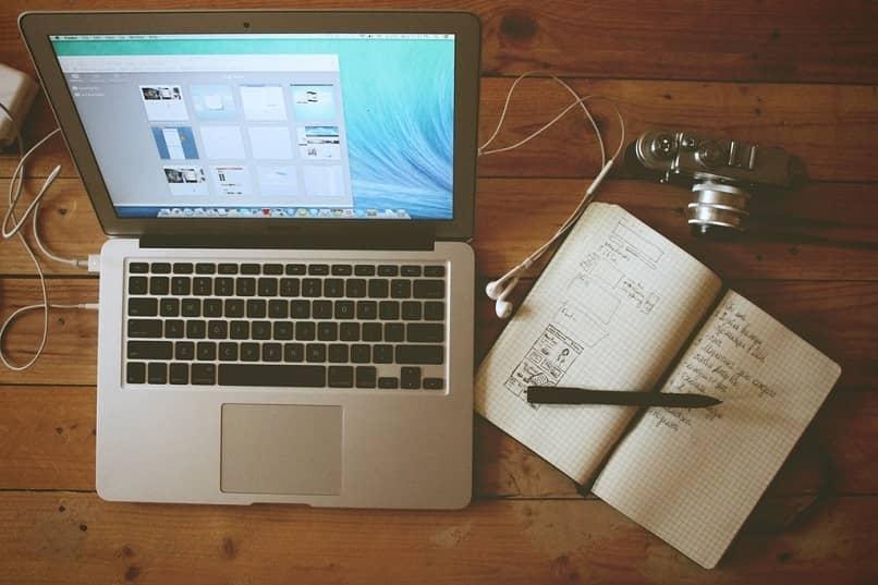 laptop en una mesa con un cuaderno