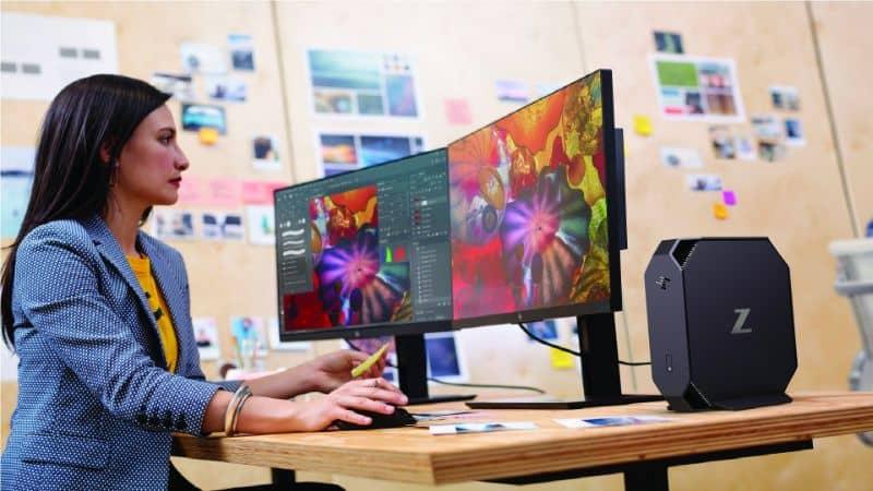 Persona que opera la computadora en un escritorio de madera