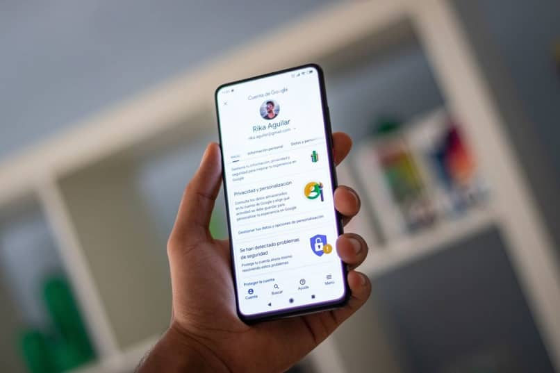 Persona que tiene un teléfono móvil en la mano con la página de configuración de una cuenta de Google