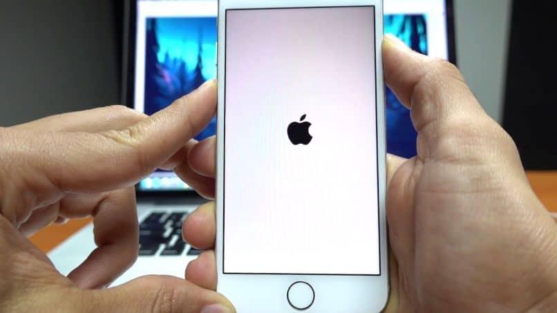 iPhone en mano con pantalla de portátil hacia atrás