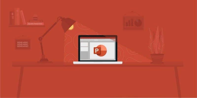portátil en la mesa con power point en la pantalla de fondo rojo oscuro