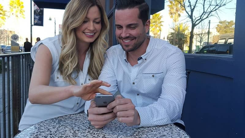 La pareja se ríe juntos viendo celular