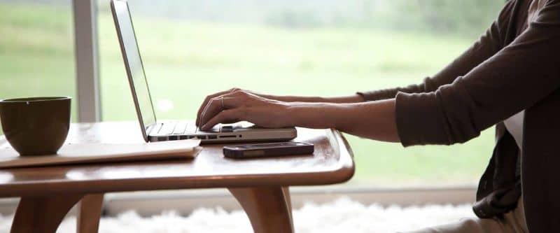 persona que conduce un portátil en una mesa con café y teléfono móvil