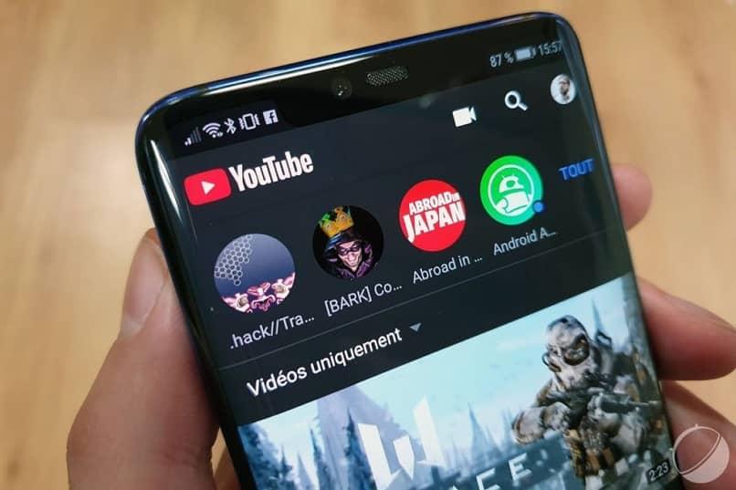 Hombre sujetando el teléfono celular que muestra la interfaz principal de Youtube