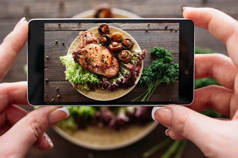 mujer tomando fotos de comida con celular