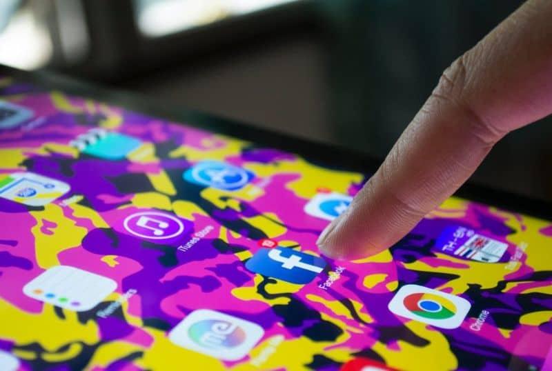 Presionando el dedo en el toque del móvil para acceder a Facebook