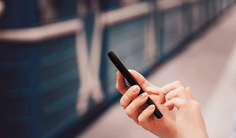 Algunas manos sostienen un teléfono móvil.