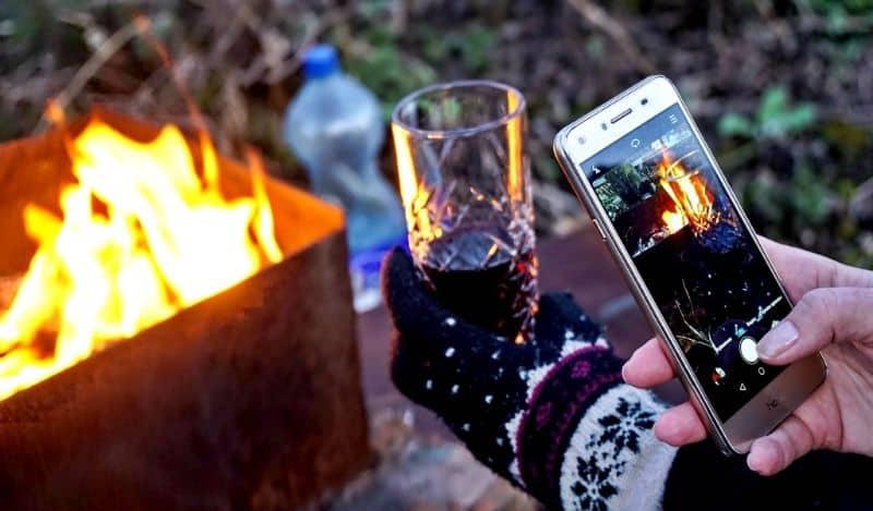 mujer tomando fotos celular y fuego