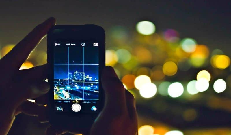 Manos tomando fotos con el iphone por la noche